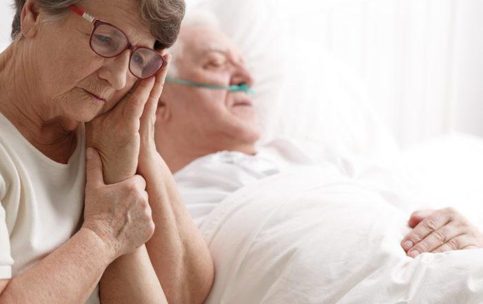 Sad senior woman holding her dying husband's hand