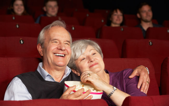 Senior Couple Watching Film In Cinema Laughing And Eating Popcorn